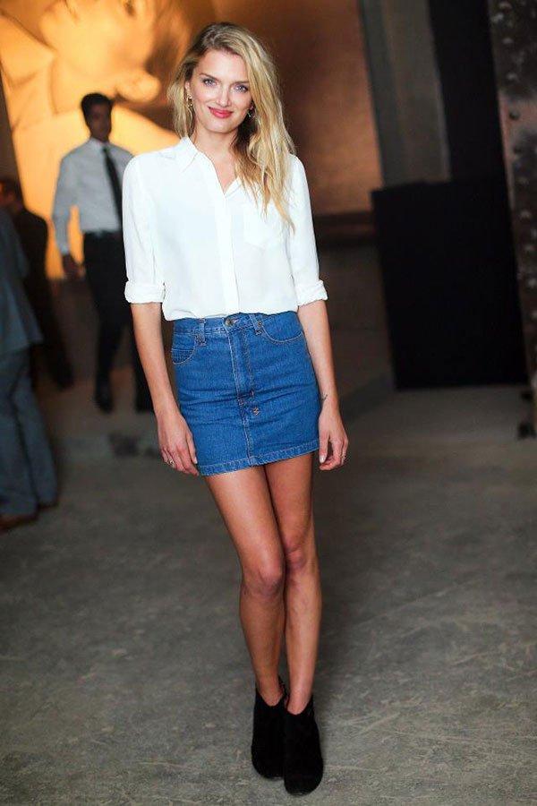 Street style de como usar saia jeans na meia estação com camisa e bota