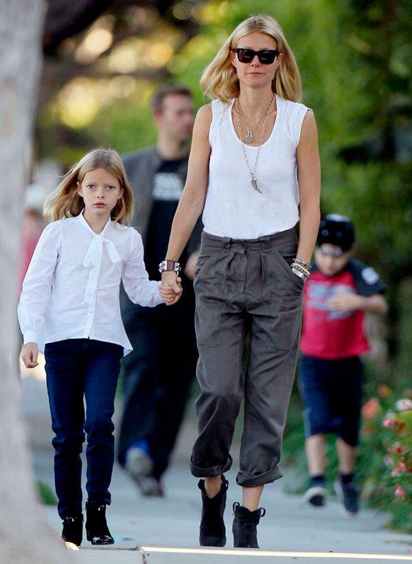 Gwyneth Paltrow passeando com a filha em look básico para o dia a dia com calça cenoura e botinha