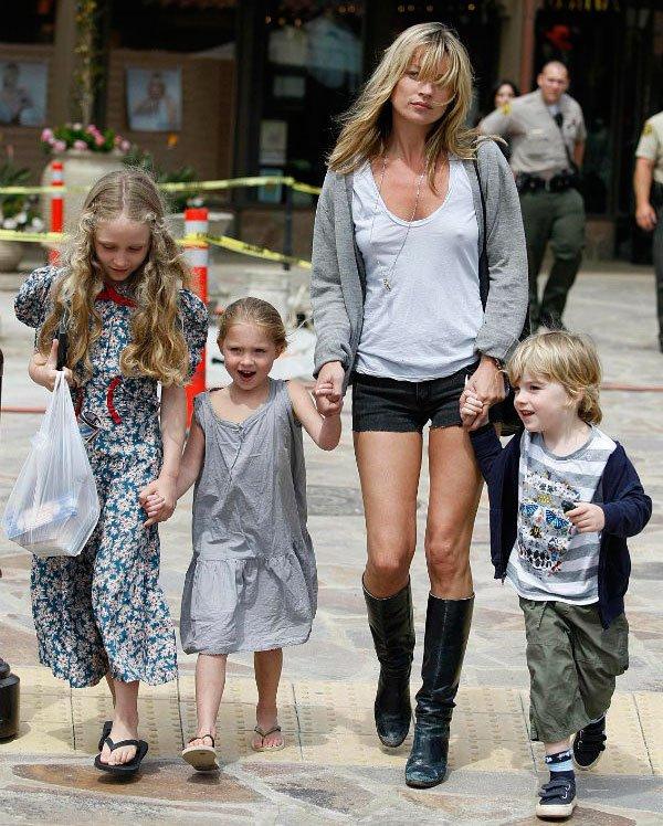 Kate Moss passeia com os filhos com look de shorts jeans, camiseta básica e botas