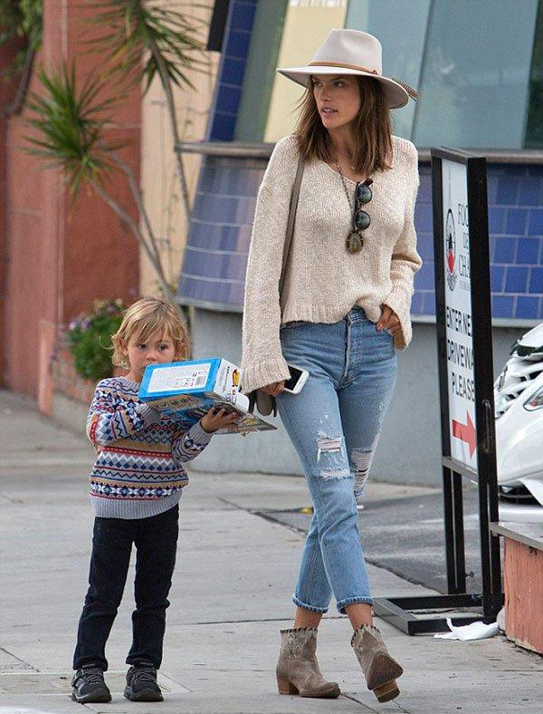 Alessandra Ambrosio passeia com filho vestindo calça jeans de cintura alta, bota, trico e chapéu