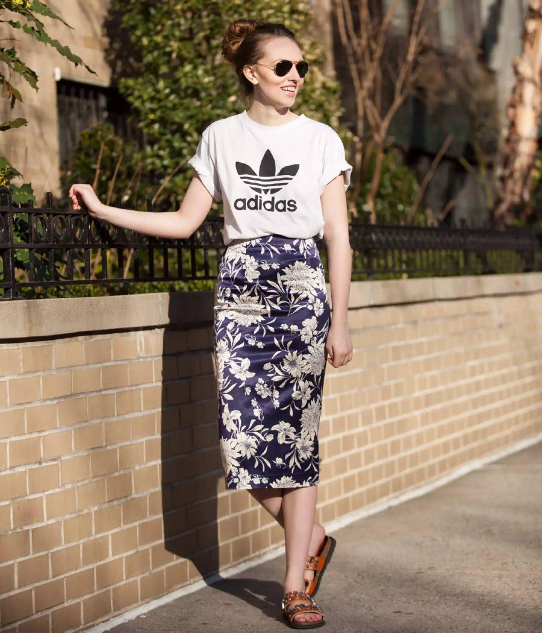 Mulher parada em frente a muro posa para foto de street style vestindo camiseta da adidas branca, saia lápis midi floral