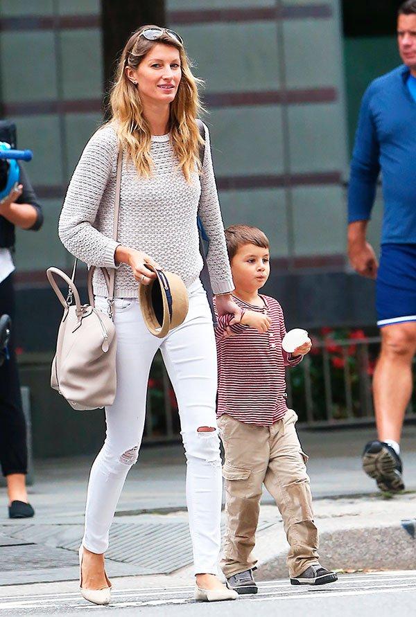 Gisele Bundchen passeia com Benjamin com look básico de jeans rasgado, sapatilhas e tricot