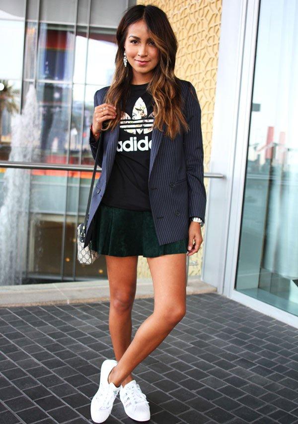 Julie Sariñana posa para foto de street style vestindo camiseta adidas, saia de camurça, blazer risca de giz, bolsa gucci e tênis adidas branco