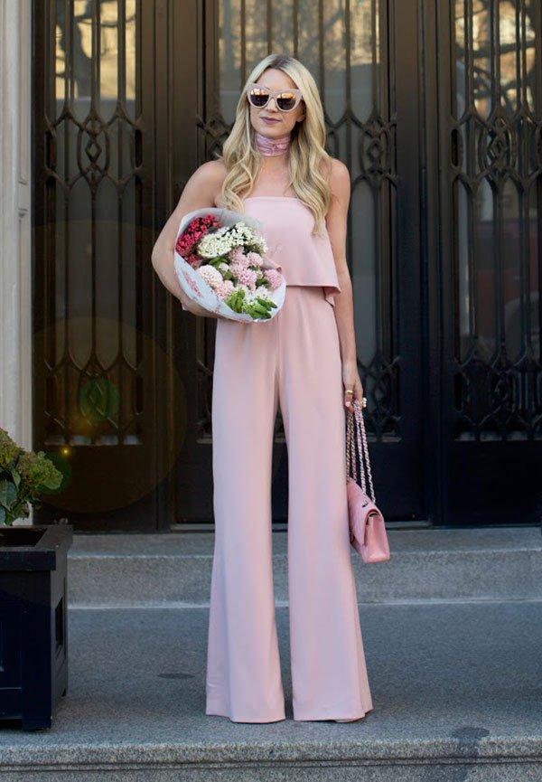 Mulher posa em frente à portão vestindo macacão rosa pastel segurando flores e Chanel