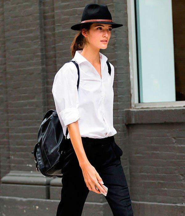 Look usando mochila de couro preto mais camisa branca e chapéu