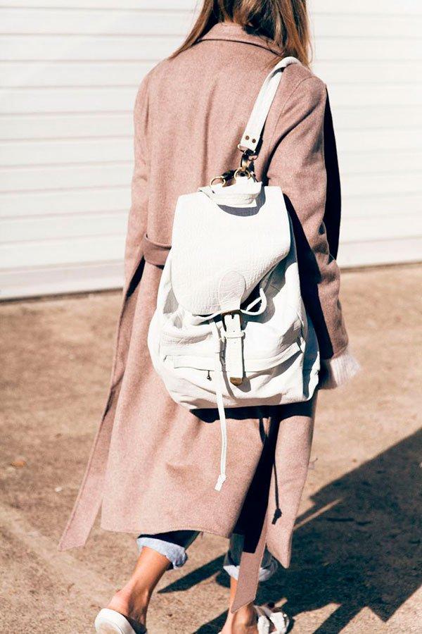 Street style com mochila de couro branca e sobretudo bege