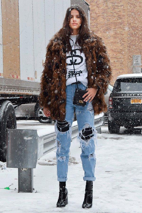 Bruna Lirio posa para foto de street style usando t-shirt branca, calça jeans rasgada, bota de verniz preta, casaco faux fur marrom