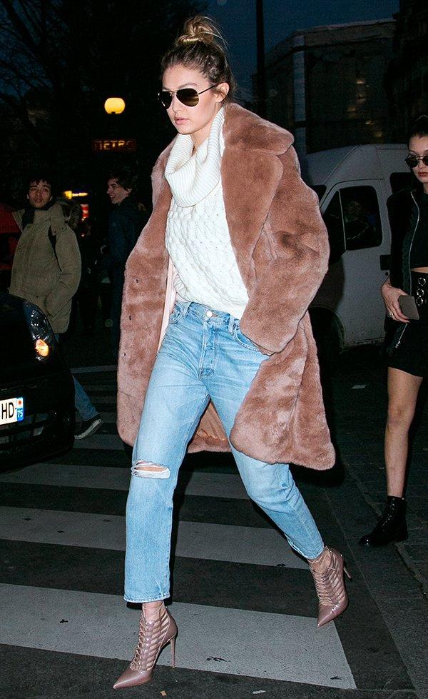 Gigi Hadid posa para foto de street style usando maxi tricot off-white, calça jeans reta, scarpin nude, casaco de pelos rosado e óculos aviador