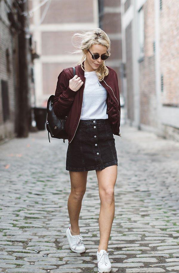 Mary Seng anda na rua usando t-shirt podrinha branca, mini saia de botões, jaqueta bomber vinho, óculos redondos, mochila de couro, tênis branco