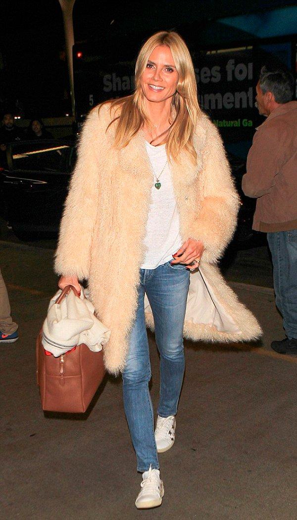 Heidi Klum posa para foto usando tshirt branca, jeans skinny, tênis branco, bolsa marrom e casaco faux fur bege