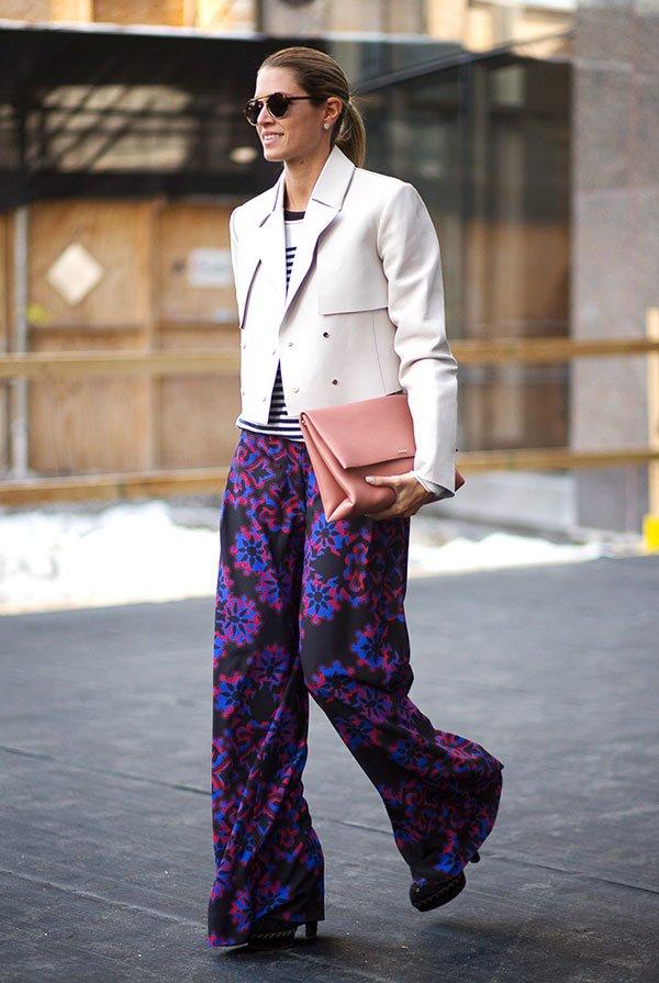 Street style look de Helena Bordon usando blusa listrada, jaqueta couro rosada, calça pantalona estampada e maxi clutch