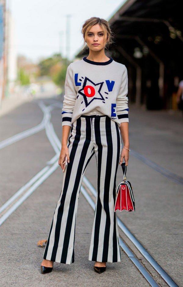 Street style look com suéter estrelas e calça flare listras