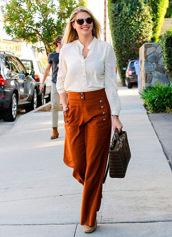 Street style look Kate Upton usando calça pantalona marrom com botões, camisa branca e mocassim.