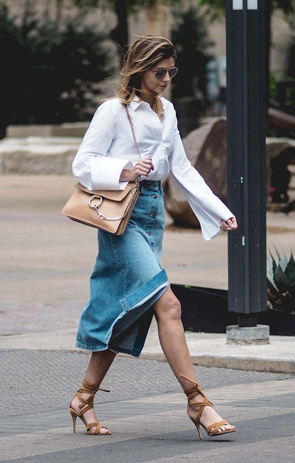 Street style look com saia midi jeans botões e camisa branca com sandália e bolsa bege