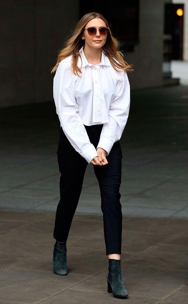 Elizabeth usa look com camisa bufante branca e calça social preta com bota cano curto