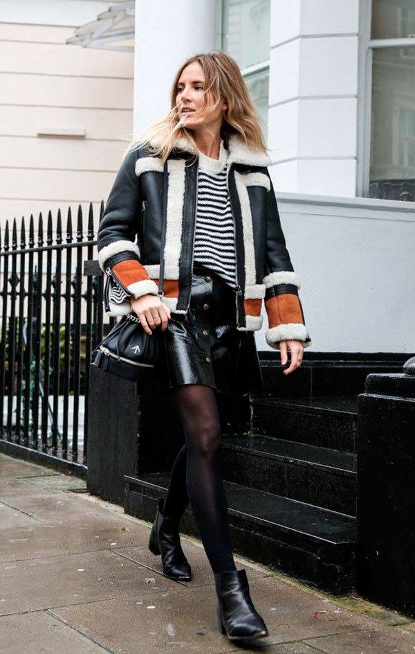 Lucy Williams caminha na rua entre casas vestindo maxi tricot de listras, saia de couro preta de botões, meia calça, botas de cano curto pretas, bolsa estilo saco e casaco de couro tricolor