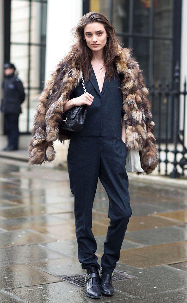Mulher posa para foto de street style usando macacão preto, botas pretas, bolsa Dior preta de couro e casaco faux fur marrom