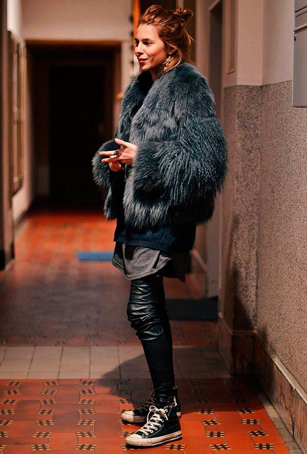 Maja Wyh posa para foto usando tshirt cinza, tricot preto, calça skinny de couro preta, casaco faux fur, tênis converse all star