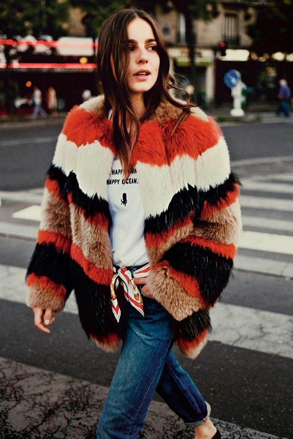 Mulher posa para foto de street style usando t-shirt branca, casaco faux fur colorido, calça jeans reta e lenço de seda