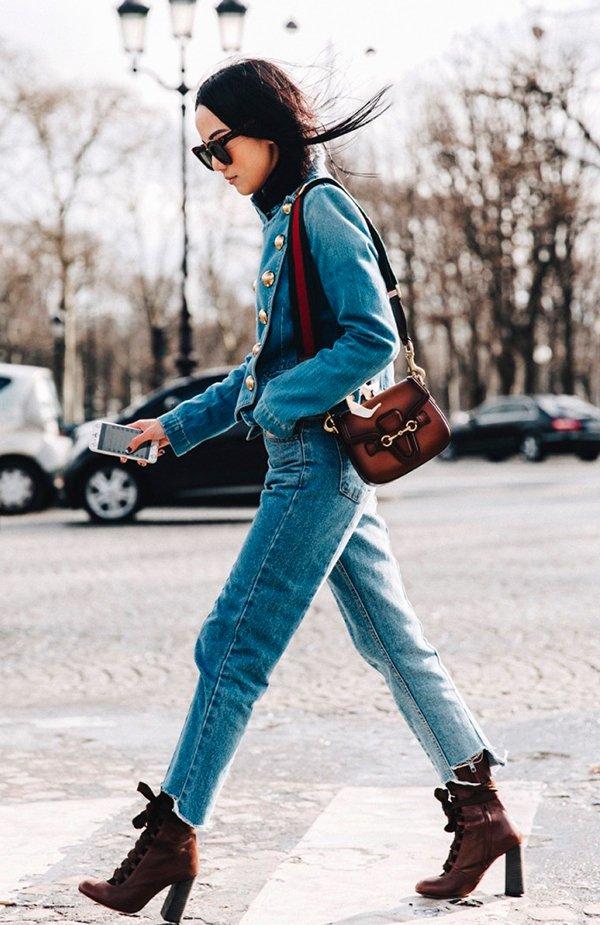 Yoyo Cao andando em Paris usando look total jeans com calça jeans vintage de modelagem reta, jaqueta de botões jeans, bota militar e bolsa Gucci