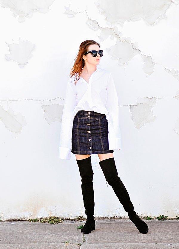 Jena Aldridge, do blog Sea Of Shoes posa para foto de street style usando camisa branca oversized, saia jeans de cintura alta de botões, óculos escuros e botas over the knee