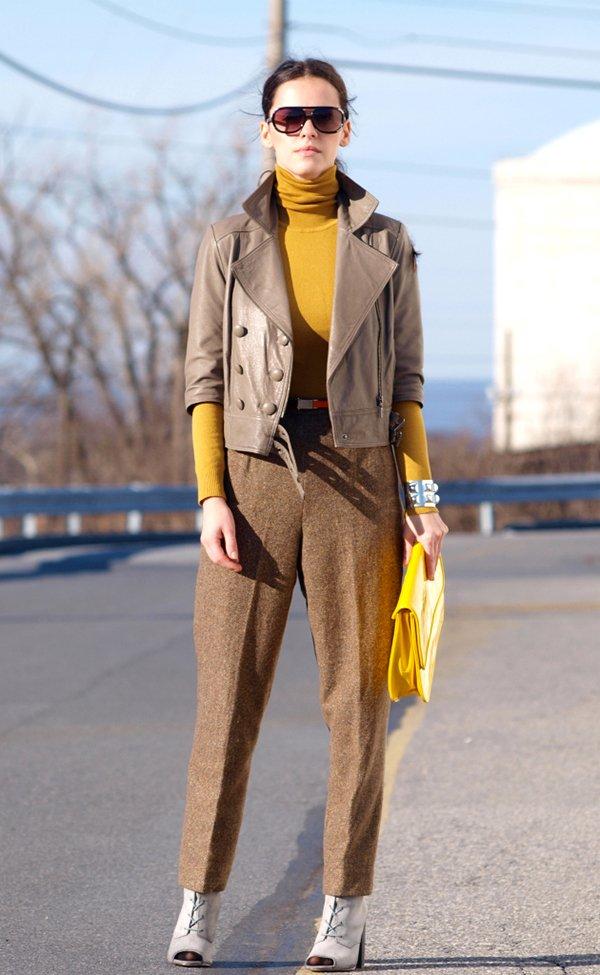 Mulher exibe look fashionista com turtleneck mostarda, calça de alfaiataria, jaqueta de couro e sandália abotinada nude