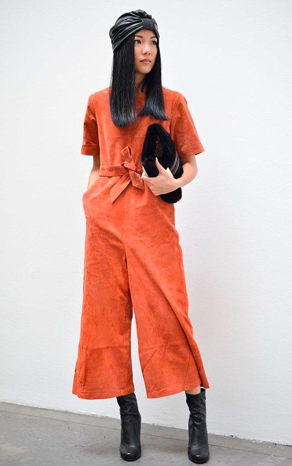 Yoyo Cao aposta no look estiloso macacão com turbante, arrematando com bota preta e clutch de pelos
