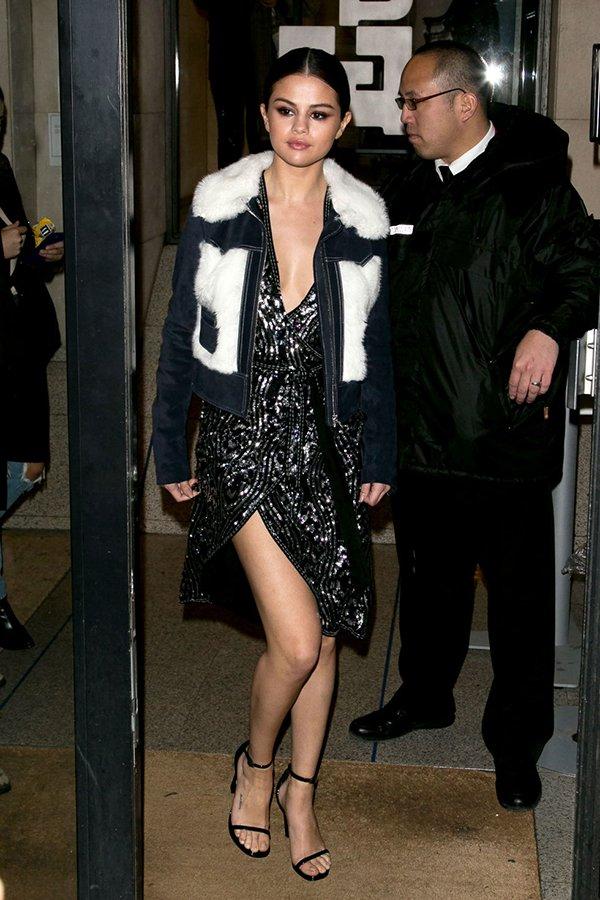 Selena Gomez investe em casaco de pelo e vestido de paete para sair