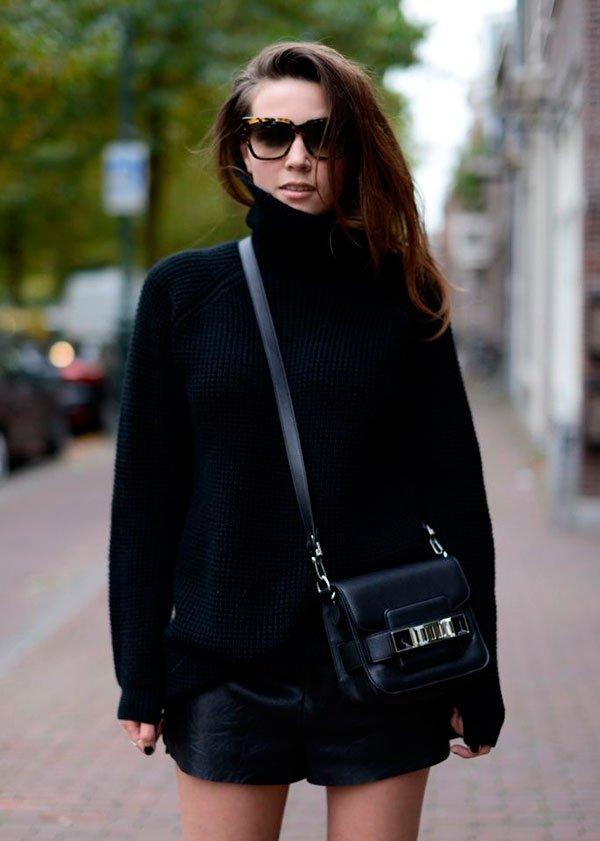 Street style look suéter preto turtleneck, shorts de couro e bolsa transversal.