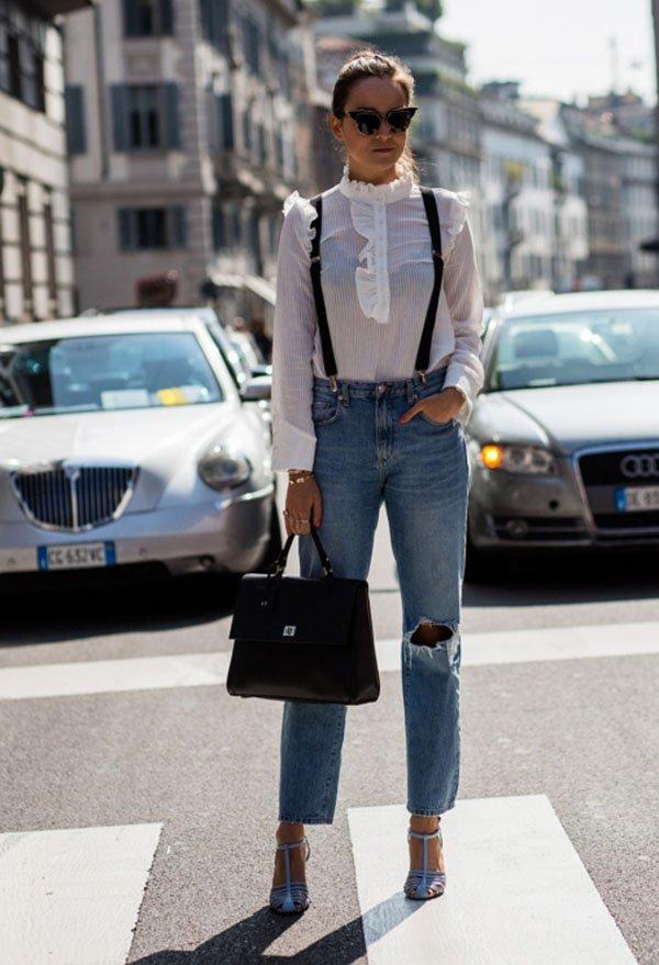 Mulher posa para foto de street style usando camisa vitoriana branca, calça jeans de cintura alta destroyed, bolsa preta, sandálias e óculos de gatinho