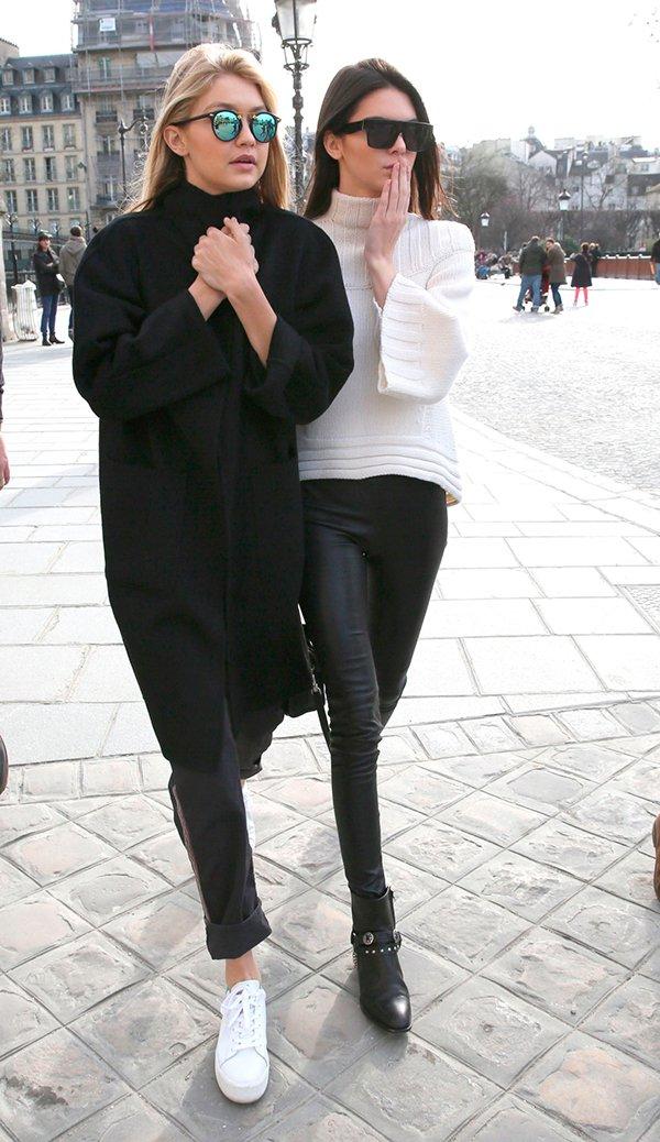 Gigi Hadid e Kendall Jenner vestem casaco preto oversized com calça de couro preta e tenis branco e tricot branco com calça de couro e botas pretas