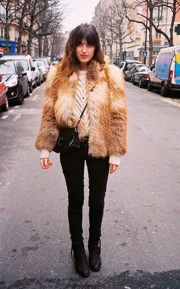 Jeanne Damas usa sueter off white, casaco de pelos marrom, calça skinny preta e botas