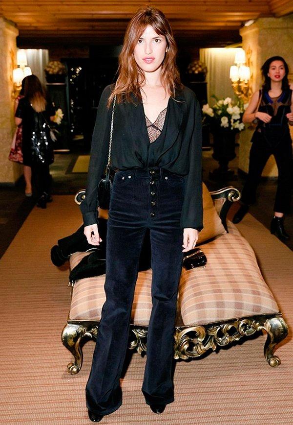 Jeanne Damas usa top de renda preto, camisa preta, calça cintura alta de veludo azul marinho, bolsa preta de alça de corrente