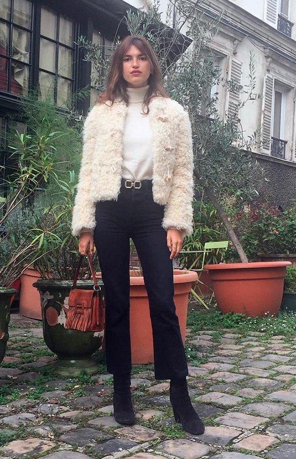 Jeanne Damas usa turtleneck de tricot nude, casaco de pelos off white, calça cropped preta, bota de camurça preta e bolsa marrom de franjas