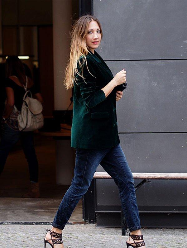 Street style look com blazer de veludo verde e calça jeans com sandália.