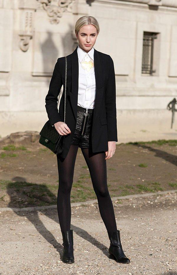 Street style look com camisa branca, shorts de couro, blazer preto, meia calça e bota.
