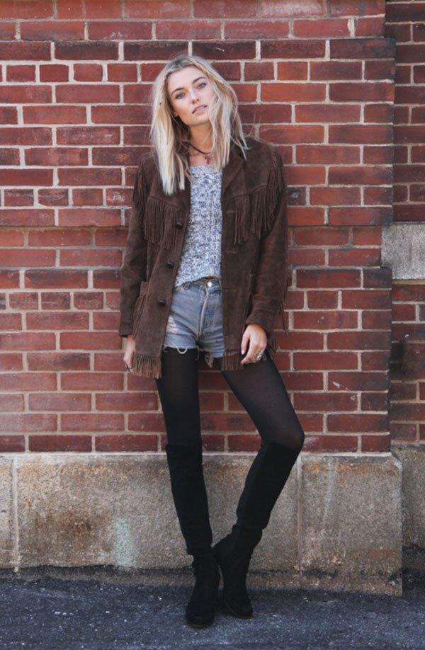 Street style look shorts jeans com meia calça, bota camurça e casaco marrom com franjas.