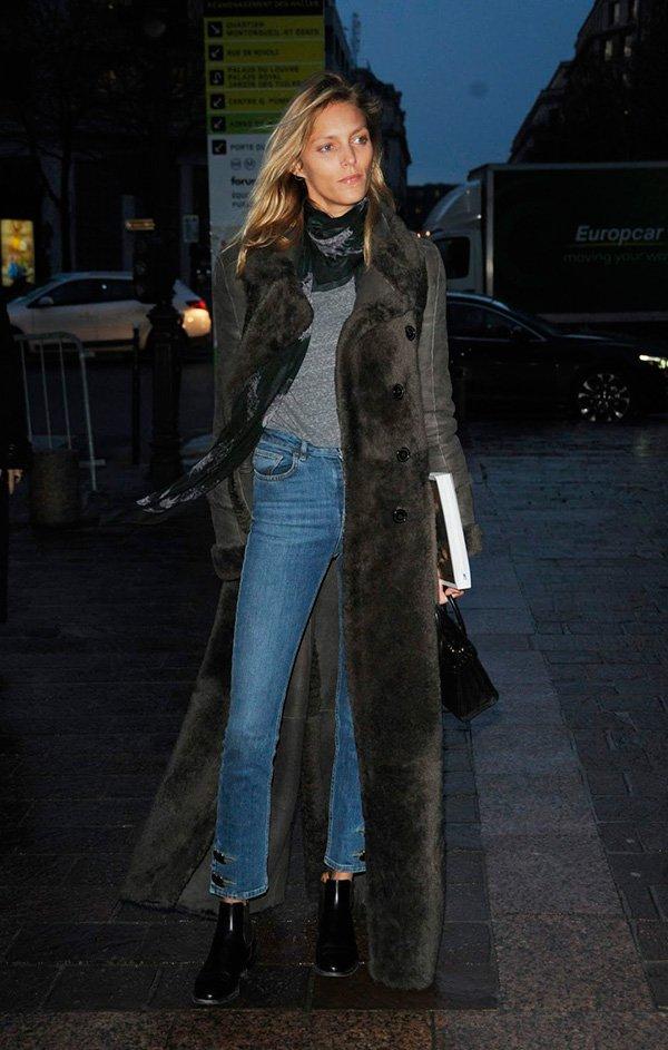 Anja Rubik street style look camiseta cinza, sobretudo e calça jeans com bota verniz.