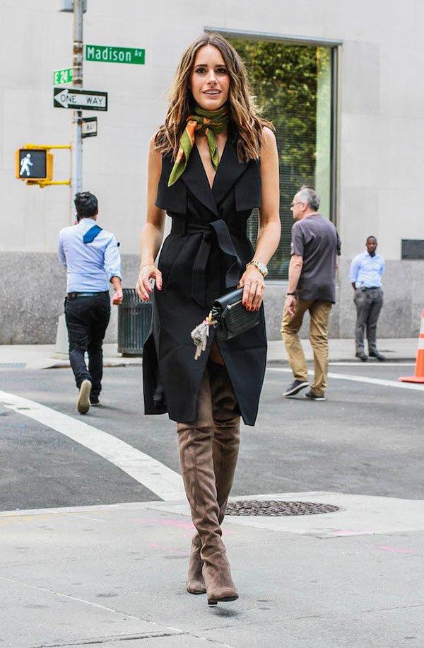 Street style look com colete longo fechado, bota over the knee marrom e lenço pescoço.