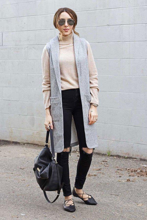 Street style look com colete longo cinza, calça preta rasgo no joelho, blusa turtleneck gola bege manga longa e sapatos amarração.