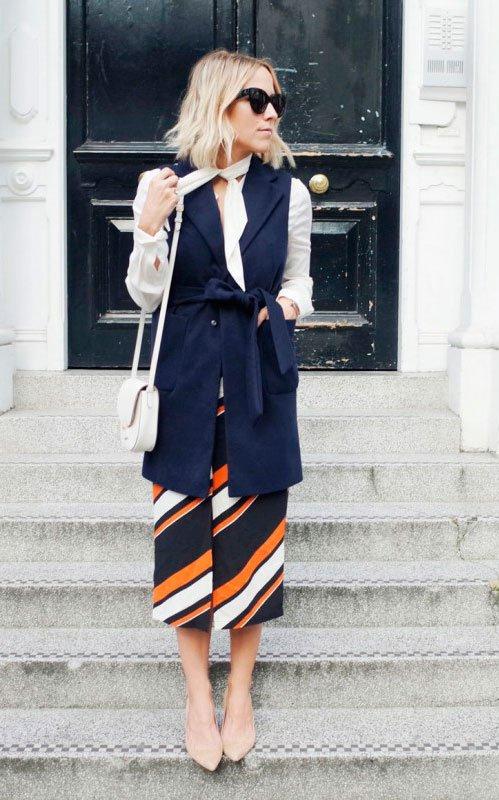Street style look com colete azul marinho, blusa manga longa laço, saia midi listras coloridas e sapato bege.