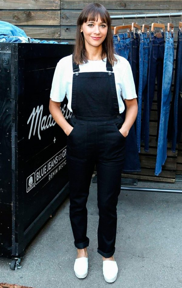 Street style look jardineira preta jeans, camiseta branca e tênis.
