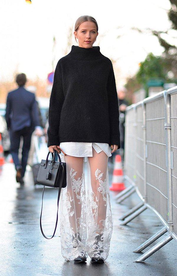 Street style look suéter preto, saia renda, camisa listrada e bota preta.