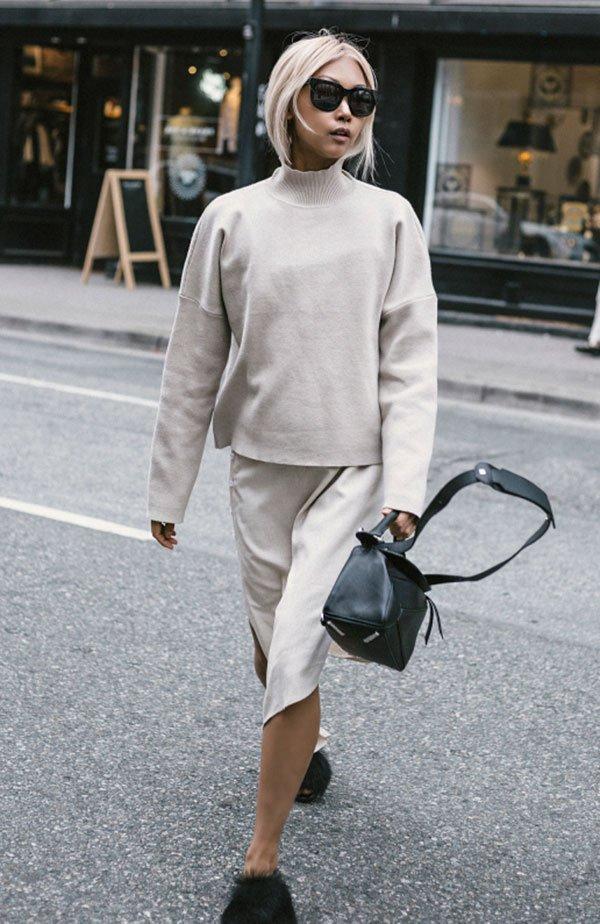 Street style look off white bege turtleneck, saia assimétrica e sapato pêlos preto.