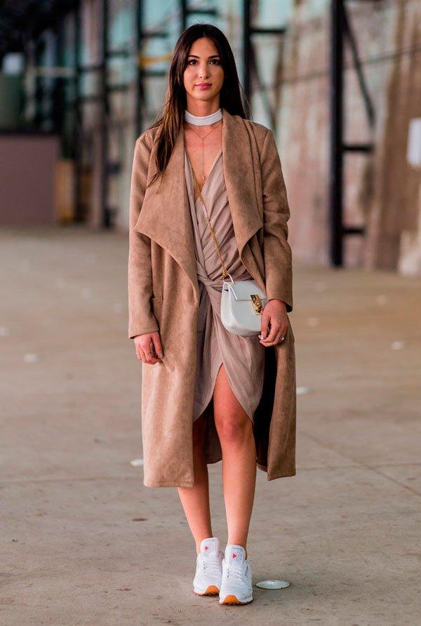 street style look marrom com vestido assimétrico com nó, skinny scarf, sobretudo e tênis branco.