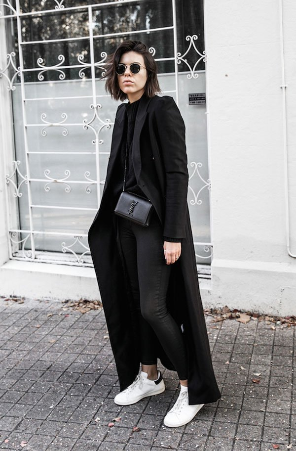 Street style look monocromático preto, calça jeans, sobretudo, bolsa YSL, óculos redondo e tênis branco.