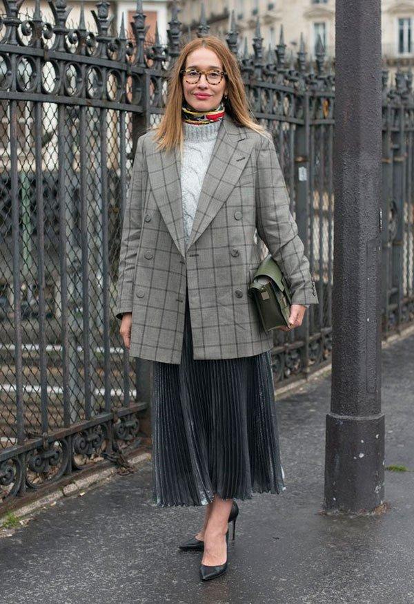Street style look com saia plissada preta, blazer xadrez, blusa gola branca e scarpin preto.