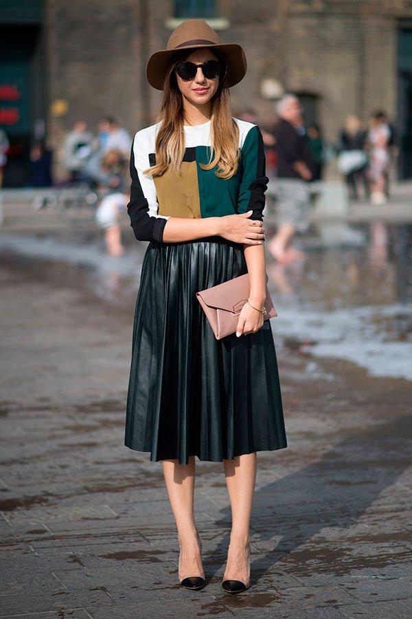 Street style look com saia plissada preta, chapéu marrom e clutch bege envelope.
