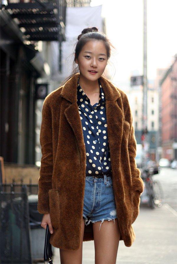 Street style look blusa poá, shorts jeans e casaco marrom pêlo.
