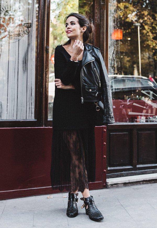 Street style look suéter preto, saia renda, jaqueta couro e bota preta.